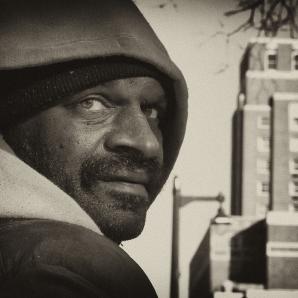 Black man in hoody looking over shoulder